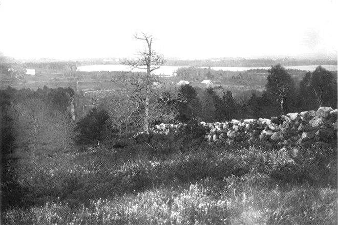 A tall stone wall divides a field on Dinsmoor Hill, Windham with Canobie lake in background.
